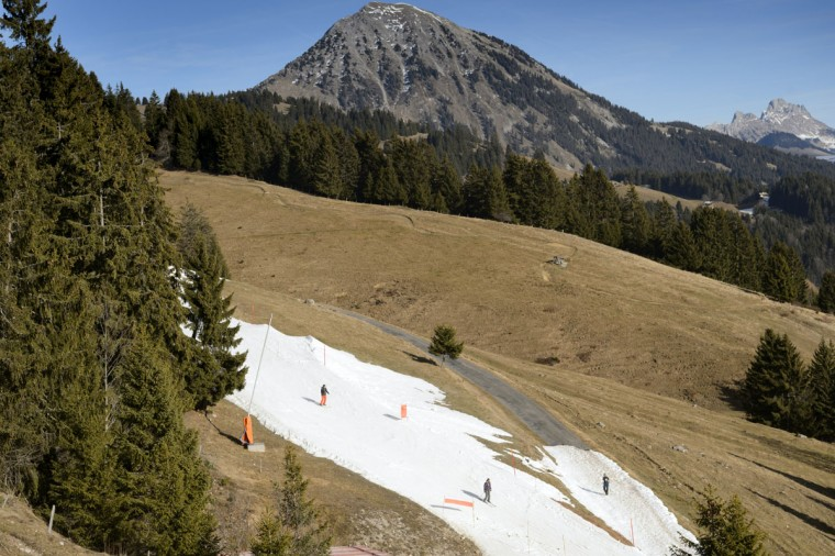 People use a ski slope covered with artificial snow surrounded by green fields in the Swiss Alps in Leysin, Switzerland on Dec. 24, 2015. (Laurent Gillieron/Keystone via AP)