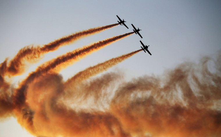 A team of aerobatics pilots perform a stunt at the World Air Games in Dubai, United Arab Emirates, on Sunday, Dec. 6, 2015. The World Air Games includes precision aerobatics, skydiving and hot air balloon competitions. (AP Photo/Jon Gambrell)