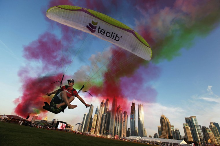 Paraguilder Ragolski Francois, 28, of France takes a practice run and leap just after an aerobatic team raced by at the World Air Games in Dubai, United Arab Emirates, on Sunday, Dec. 6, 2015. The World Air Games includes precision aerobatics, skydiving and hot air balloon competitions. (AP Photo/Jon Gambrell)