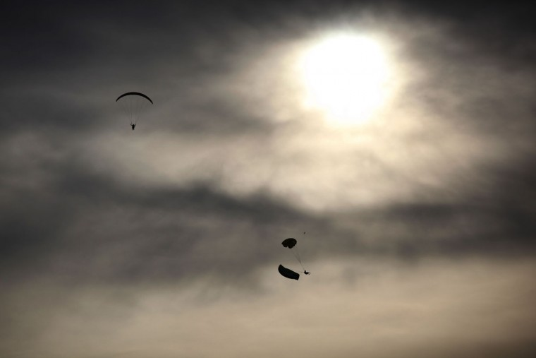 Paraguilders perform stunts against the setting sun at the World Air Games in Dubai, United Arab Emirates, on Sunday, Dec. 6, 2015. The World Air Games includes precision aerobatics, skydiving and hot air balloon competitions. (AP Photo/Jon Gambrell)