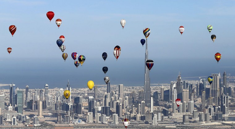 "Hot air balloons fly over Dubai during the World Air Games 2015, held under the rules of the Federation Aeronautique International (FAI) as part of the ""Dubai International Balloon Fiesta"" event on December 9, 2015. (KARIM SAHIB/AFP/Getty Images)"