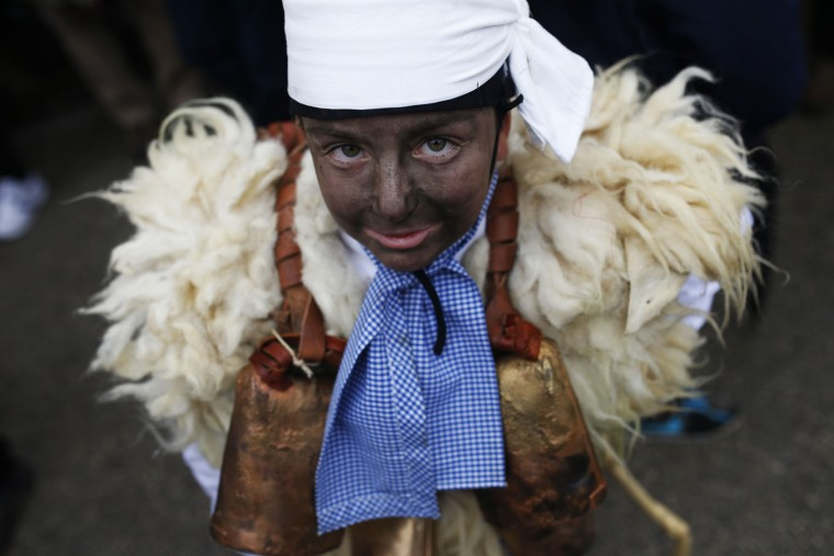 """A young boy dressed in sheepskin with jingling bells to make noise, and so called """"Zamarraco"""" poses for a photograph during the Vijanera Festival, in the small village of Silio, northern Spain, Sunday, Jan. 3, 2016. The Vijanera masquerade, of pre-Roman origin, is the first carnival of the year in Europe symbolizing the triumph of good over evil and involving the participation of crowds of residents wearing different masks, animal skins and brightly coloured clothing with its own complex function and symbolism and becoming the living example of the survival of archaic cults to nature. (AP Photo/Francisco Seco)"""