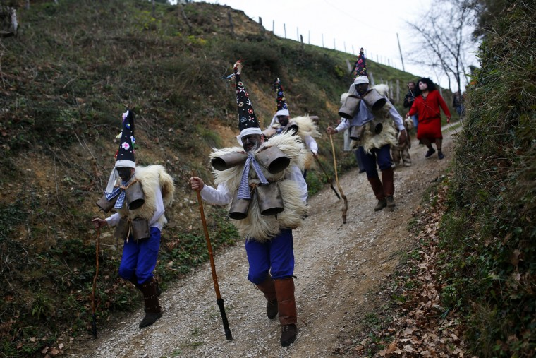 """Men dressed in sheepskins and jingling bells to make noise, and so called """"Zamarracos,"""" march during the Vijanera Festival, in the small village of Silio, northern Spain, Sunday, Jan. 3, 2016. The Vijanera masquerade, of pre-Roman origin, is the first carnival of the year in Europe symbolizing the triumph of good over evil and involving the participation of crowds of residents wearing different masks, animal skins and brightly coloured clothing with its own complex function and symbolism and becoming the living example of the survival of archaic cults to nature. (AP Photo/Francisco Seco)"""
