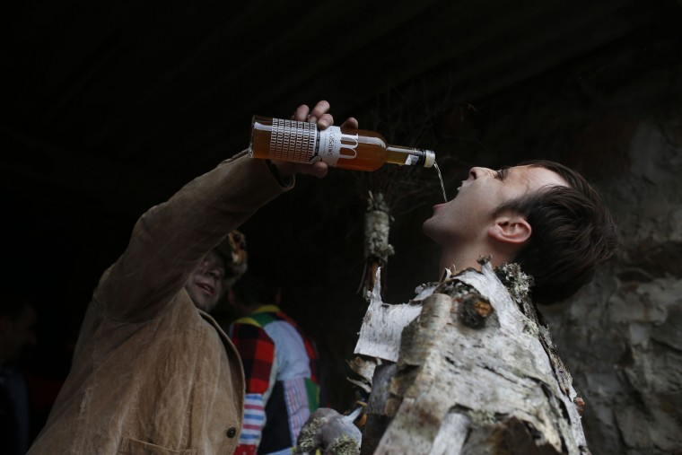 A man dressed with a costume drinks liquor before taking part in the Vijanera Festival, in the small village of Silio, northern Spain, Sunday, Jan. 3, 2016. The Vijanera masquerade, of pre-Roman origin, is the first carnival of the year in Europe symbolizing the triumph of good over evil and involving the participation of crowds of residents wearing different masks, animal skins and brightly coloured clothing with its own complex function and symbolism and becoming the living example of the survival of archaic cults to nature. (AP Photo/Francisco Seco)