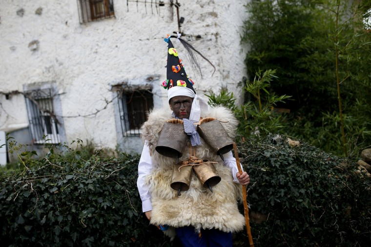 """A man dressed in sheepskins with jingling bells to make noise, and so called """"Zamarraco,"""" poses for a photograph during the Vijanera Festival, in the small village of Silio, northern Spain, Sunday, Jan. 3, 2016. The Vijanera masquerade, of pre-Roman origin, is the first carnival of the year in Europe symbolizing the triumph of good over evil and involving the participation of crowds of residents wearing different masks, animal skins and brightly coloured clothing with its own complex function and symbolism and becoming the living example of the survival of archaic cults to nature. (AP Photo/Francisco Seco)"""
