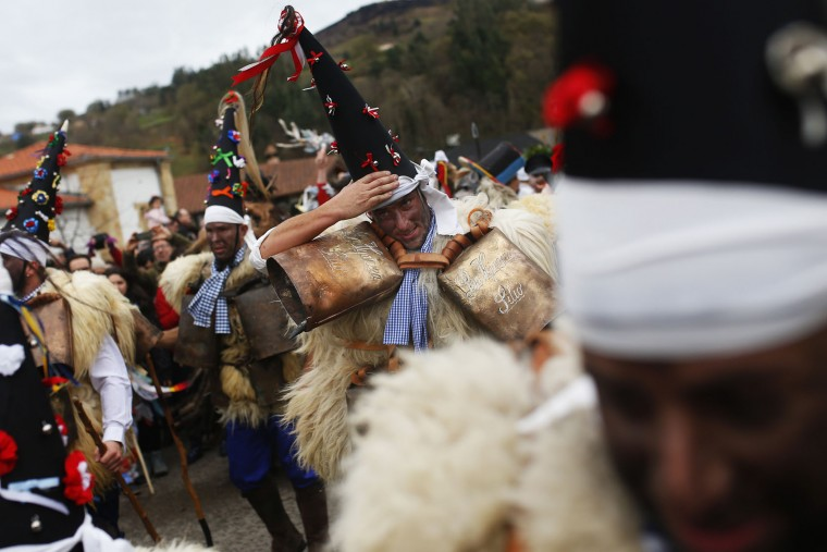 """Men dressed in sheepskins and jingling bells to make noise, and so called """"Zamarracos"""", march during the Vijanera Festival, in the small village of Silio, northern Spain, Sunday, Jan. 3, 2016. The Vijanera masquerade, of pre-Roman origin, is the first carnival of the year in Europe symbolizing the triumph of good over evil and involving the participation of crowds of residents wearing different masks, animal skins and brightly coloured clothing with its own complex function and symbolism and becoming the living example of the survival of archaic cults to nature. (AP Photo/Francisco Seco)"""