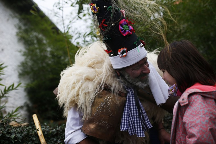 """A man, so called """"Zamarraco,"""" dressed in sheepskins and bells to make noise, talks to a young girl during the Vijanera Festival, in the small village of Silio, northern Spain, Sunday, Jan. 3, 2016. The Vijanera masquerade, of pre-Roman origin, is the first carnival of the year in Europe symbolizing the triumph of good over evil and involving the participation of crowds of residents wearing different masks, animal skins and brightly coloured clothing with its own complex function and symbolism and becoming the living example of the survival of archaic cults to nature. (AP Photo/Francisco Seco)"""