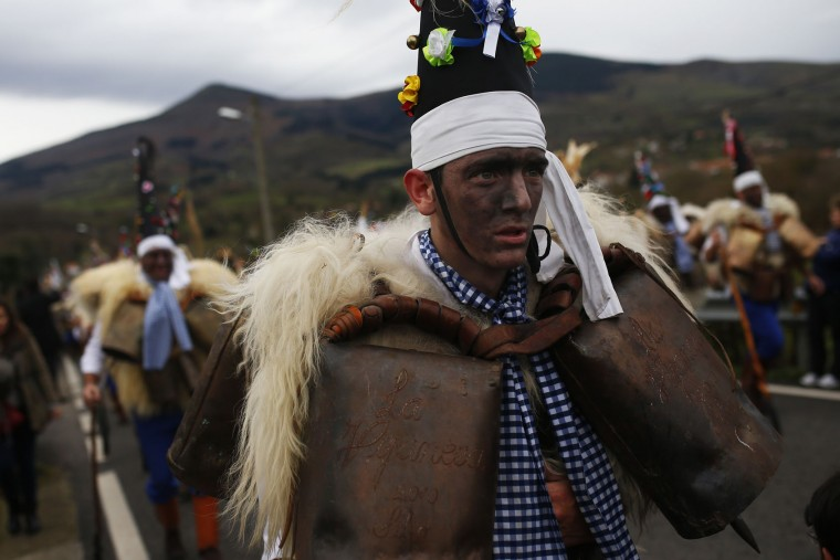 """A man, so called """"Zamarraco,"""" dressed in sheepskins and bells to make noise, marches with others during the Vijanera Festival, in the small village of Silio, northern Spain, Sunday, Jan. 3, 2016. The Vijanera masquerade, of pre-Roman origin, is the first carnival of the year in Europe symbolizing the triumph of good over evil and involving the participation of crowds of residents wearing different masks, animal skins and brightly coloured clothing with its own complex function and symbolism and becoming the living example of the survival of archaic cults to nature. (AP Photo/Francisco Seco)"""