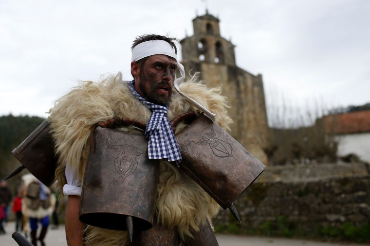 """A man, so called """"Zamarraco,"""" dressed in sheepskins with jingling bells to make noise, marches with others during the Vijanera Festival, in the small village of Silio, northern Spain, Sunday, Jan. 3, 2016. The Vijanera masquerade, of pre-Roman origin, is the first carnival of the year in Europe symbolizing the triumph of good over evil and involving the participation of crowds of residents wearing different masks, animal skins and brightly coloured clothing with its own complex function and symbolism and becoming the living example of the survival of archaic cults to nature. (AP Photo/Francisco Seco)"""