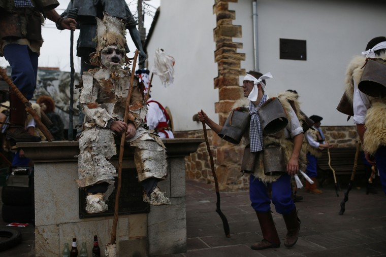 """A man, so called """"Zamarraco,"""" right, dressed in sheepskins and jingling bells to make noise, dances next to another dressed as a """"Trapajon"""", left, representing entities of nature, during the Vijanera Festival, in the small village of Silio, northern Spain, Sunday, Jan. 3, 2016. The Vijanera masquerade, of pre-Roman origin, is the first carnival of the year in Europe symbolizing the triumph of good over evil and involving the participation of crowds of residents wearing different masks, animal skins and brightly coloured clothing with its own complex function and symbolism and becoming the living example of the survival of archaic cults to nature. (AP Photo/Francisco Seco)"""