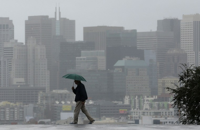 Richard Polich crosses a street in the rain on Tuesday, Jan. 5, 2016, in San Francisco. El Nino storms lined up in the Pacific, promising to drench parts of the West for more than two weeks and increasing fears of mudslides and flash floods in regions stripped bare by wildfires. Stronger systems are predicted starting Tuesday following light rain a day earlier. (AP Photo/Jeff Chiu)