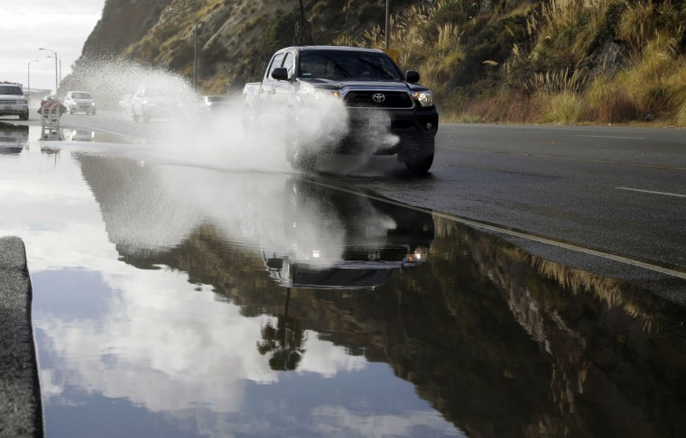 A pickup truck makes is way down a flooded road along the Pacific Coat Highway in Malibu, Calif. after a heavy rain on Tuesday, Jan. 5, 2016. Californians were warned against abandoning conservation efforts Tuesday as several weeks of storms spawned by El Nino began hitting the West Coast. Heavy rain and snow are welcome after four years of drought in California, despite their potential for causing flash floods and mudslides. (AP Photo/Nick Ut)