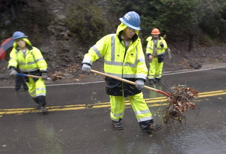 Workers with the California Conservation Corps clean debris from drains as heavy rains fall, Tuesday, Jan. 5, 2016, in Silverado, Calif. Californians were warned against abandoning conservation efforts Tuesday as several weeks of storms spawned by El Nino began hitting the West Coast. Heavy rain and snow are welcome after four years of drought in California, despite their potential for causing flash floods and mudslides. (Mindy Schauer/The Orange County Register via AP)