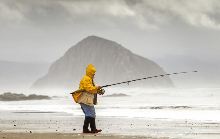 A fisherman casts his line into the stormy surf north of Morro Rock Tuesday, Jan. 5, 2016, in Morro Bay, Calif., as El Nino storms began hitting the West Coast. (Joe Johnston/The Tribune (of San Luis Obispo)