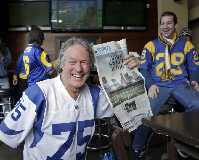 Rams fan Don Kirst holds a copy of the Los Angeles Daily News celebrating the impending return of the NFL football team to Los Angeles, at Big Wangs sports bar in the North Hollywood area of Los Angeles Wednesday, Jan. 13, 2016. League owners voted Tuesday to allow the St. Louis Rams to move to Los Angeles starting next season. (AP Photo/Nick Ut)