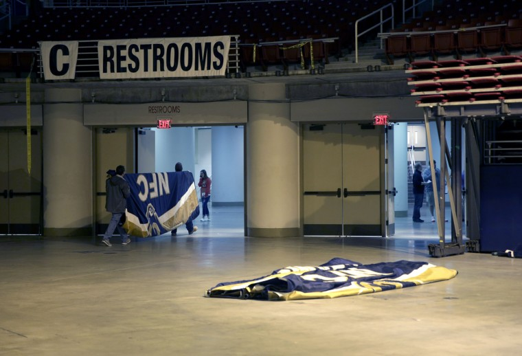 Workers carry away a Championship banner after it was removed from the ceiling of the Edward Jones Dome, former home of the St. Louis Rams football team, Thursday, Jan. 14, 2016, in St. Louis. The Rams will begin playing in Los Angeles starting with the 2016 season. (AP Photo/Jeff Roberson)