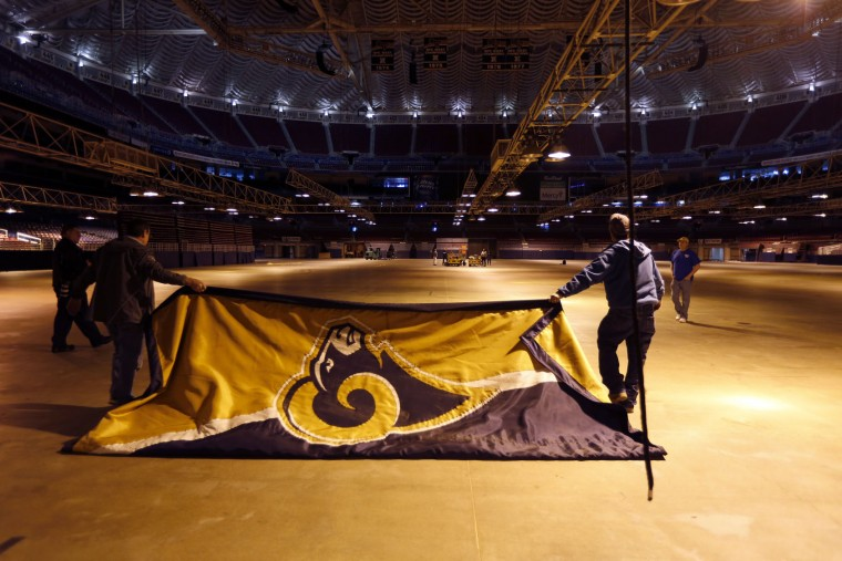 Workers remove banners from the Edward Jones Dome, former home of the St. Louis Rams football team, Thursday, Jan. 14, 2016, in St. Louis. The Rams will begin playing in Los Angeles starting with the 2016 season. (AP Photo/Jeff Roberson)