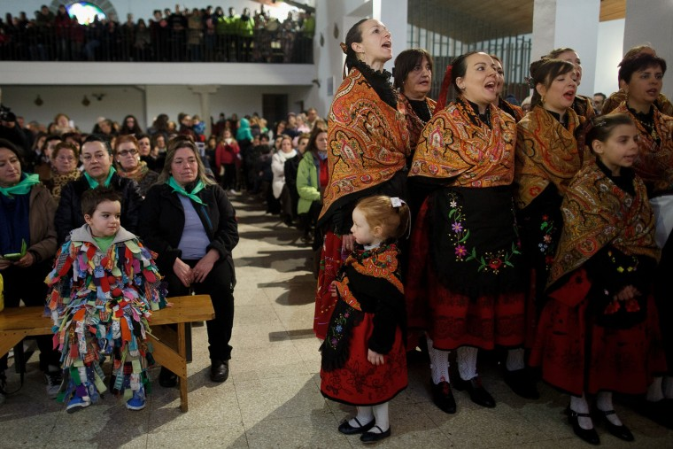 A boy dressed as Jarramplas looks at a girl while women sing during mass at a church during the Jarramplas Festival on January 20, 2016 in Piornal, Caceres province, Spain. The centuries old Jarramplas festival takes place annually every January 19-20 on Saint Sebastian Day and this year they expect to use more than 20 thousand kilogrames of turnips. Even though the exact origins of the festival are not known, various theories exist including the mythological punishment of Caco by Hercules, a relation to ceremonies celebrated by the American Indians that were seen by the first conquerors, to a cattle thief ridiculed and expelled by his village neighbours. It is generally believed to symbolize the expulsion of everything bad. (Pablo Blazquez Dominguez/Getty Images)