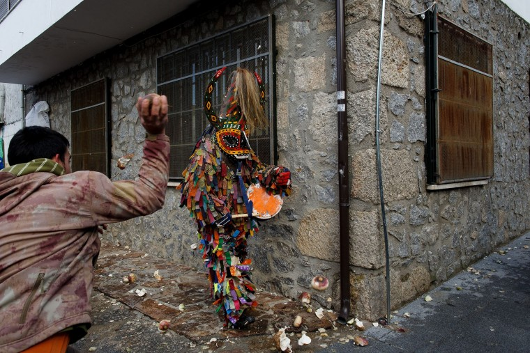 A man throws a turnip at the Jarramplas as he makes his way through the streets beating his drum during the Jarramplas Festival on January 20, 2016 in Piornal, Caceres province, Spain. The centuries old Jarramplas festival takes place annually every January 19-20 on Saint Sebastian Day and this year they expect to use more than 20 thousand kilogrames of turnips. Even though the exact origins of the festival are not known, various theories exist including the mythological punishment of Caco by Hercules, a relation to ceremonies celebrated by the American Indians that were seen by the first conquerors, to a cattle thief ridiculed and expelled by his village neighbours. It is generally believed to symbolize the expulsion of everything bad. (Pablo Blazquez Dominguez/Getty Images)