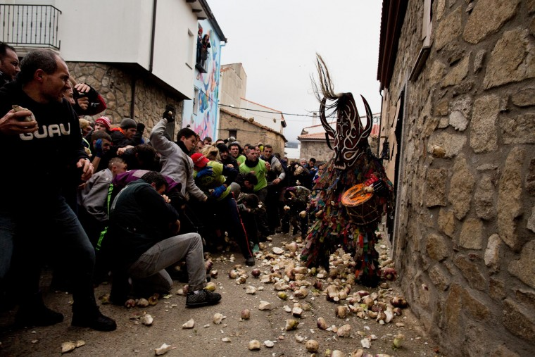 People throw turnips at the Jarramplas as he makes his way through the streets beating his drum during the Jarramplas Festival on January 20, 2016 in Piornal, Caceres province, Spain. The centuries old Jarramplas festival takes place annually every January 19-20 on Saint Sebastian Day and this year they expect to use more than 20 thousand kilogrames of turnips. Even though the exact origins of the festival are not known, various theories exist including the mythological punishment of Caco by Hercules, a relation to ceremonies celebrated by the American Indians that were seen by the first conquerors, to a cattle thief ridiculed and expelled by his village neighbours. It is generally believed to symbolize the expulsion of everything bad. (Pablo Blazquez Dominguez/Getty Images)