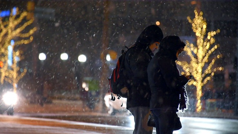 People check their smart phones on Pratt Street, while light snow falls in downtown Baltimore as people head for home and bed for the evening, as a precursor to a forecasted potential blizzard that is expected in less than two days. (Karl Merton Ferron/Baltimore Sun)