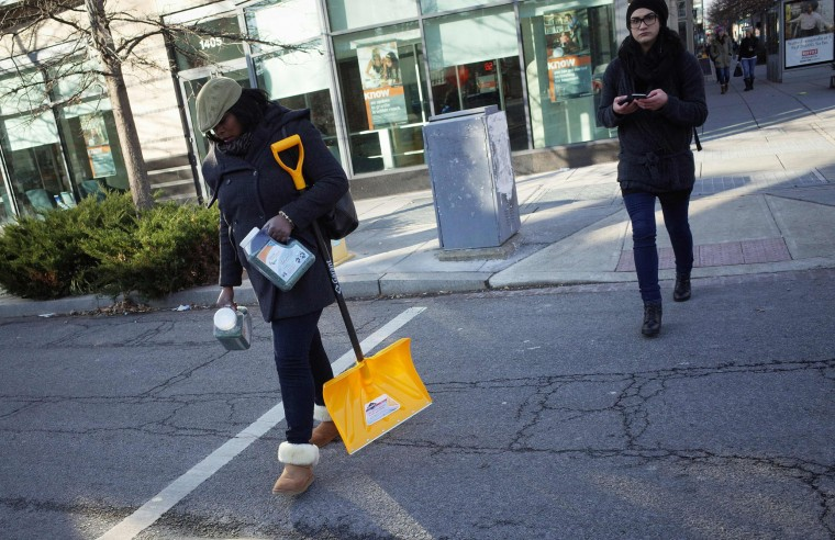 A woman carries a snow shovel and jugs of salt while crossing a street on January 21, 2016 ahead of an expected blizard in Washington, DC. A blizzard warning has been issued for the Washington region with a forecast of 2 feet, 61 cm, of snow.(Mandel Ngan/AFP/Getty Images)
