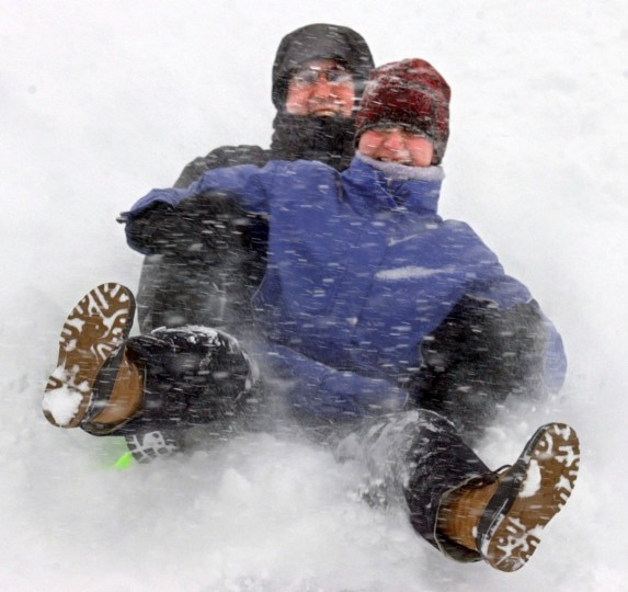 February 16, 2003 -- Linda Hayrapetian, front, and Thomas White slide down the side of Federal Hill Suday afternoon as the snow and wind sent the wind chill below zero. (John Makely/Baltimore Sun)