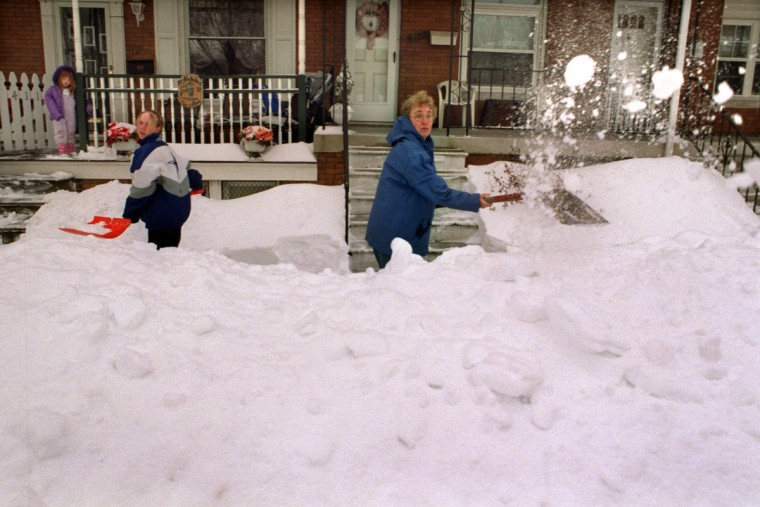 February 17, 2003 - Elizabeth Haggerty, at left, was helping her grandmother, Stephanie McNicholas, at right, dig out in front of their home in the 4100 block of Falls Road in Hampden. Watching from the porch at left is Haggerty's daughter, Colleen. (Amy Davis/Baltimore Sun)