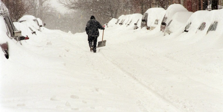 February 17, 2003 --  A man holds a snow shovel at arms length as he walks in a tire track up an unplowed South Wolfe St. (Jed Kirschbaum/Baltimore Sun)