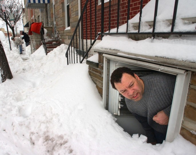 February 17, 2003 --  Little Italy resident Rick Carter looks out towards the street from his downstairs family room door as his neighbors begin digging out their cars and sidewalks Monday afternoon. (John Makely/Baltimore Sun)