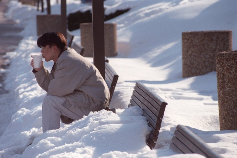 January 14, 1996 -- Sam Kim of Baltimore takes a break from his studies at Johns Hopkins University to enjoy a hot drink and the warm sun on one of the few benches that had no snow outside the Light St. Pavilion of Harborplace. He felt cooped up being inside on such a mild day, so he ventured to the inner harbor. (Karl Merton Ferron/Baltimore Sun)