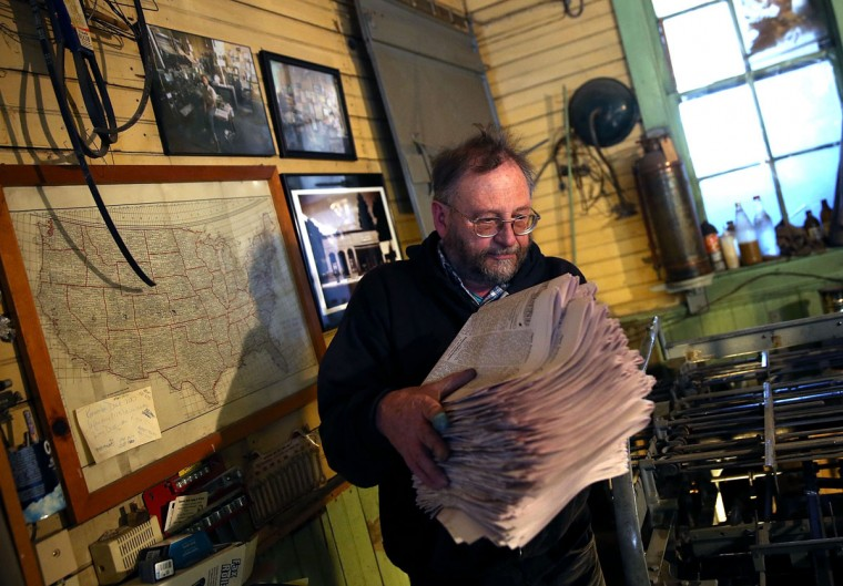 Saguache Crescent owner and editor Dean Coombs carries freshly printed copies of the Saguache Crescent newspaper on January 19, 2016 in Saguache, Colorado. The Saguache Crescent newspaper is the last newspaper in the United States that is produced using a Linotype hot metal typesetting machine. Dean Coombs, the paper's owner and editor, has been publishing the small town newspaper once a week using a Linotype machine that was purchased new in 1921, a few years after his family took over the paper in 1917. Coombs has been running the business by himself for the past 38 years and has no plans of shutting its doors anytime soon. Most newspapers discontinued the use of Linotypes over 40 years ago and were replaced with offset lithography printing and computer typesetting. (Photo by Justin Sullivan/Getty Images)