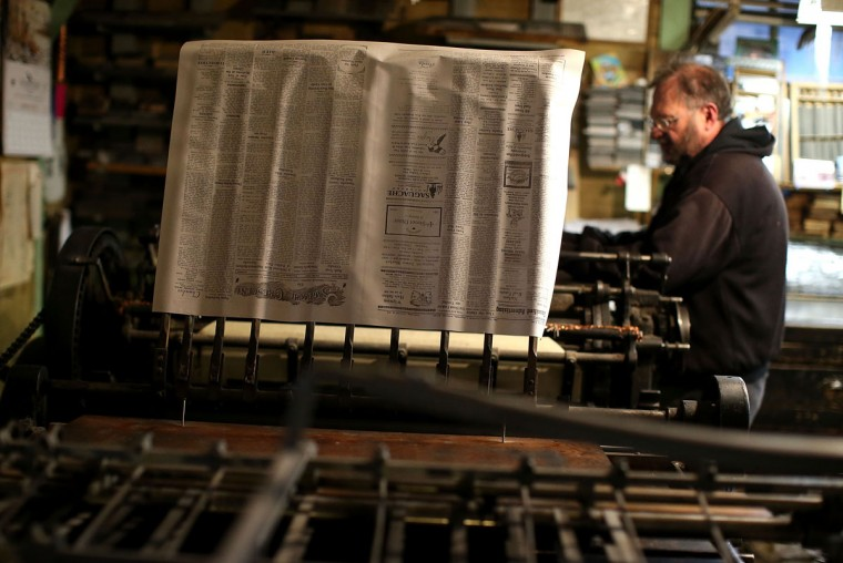 A freshly printed copy of the Saguache Crescent rolls off of the press on January 19, 2016 in Saguache, Colorado. The Saguache Crescent newspaper is the last newspaper in the United States that is produced using a Linotype hot metal typesetting machine. Dean Coombs, the paper's owner and editor, has been publishing the small town newspaper once a week using a Linotype machine that was purchased new in 1921, a few years after his family took over the paper in 1917. Coombs has been running the business by himself for the past 38 years and has no plans of shutting its doors anytime soon. Most newspapers discontinued the use of Linotypes over 40 years ago and were replaced with offset lithography printing and computer typesetting. (Photo by Justin Sullivan/Getty Images)