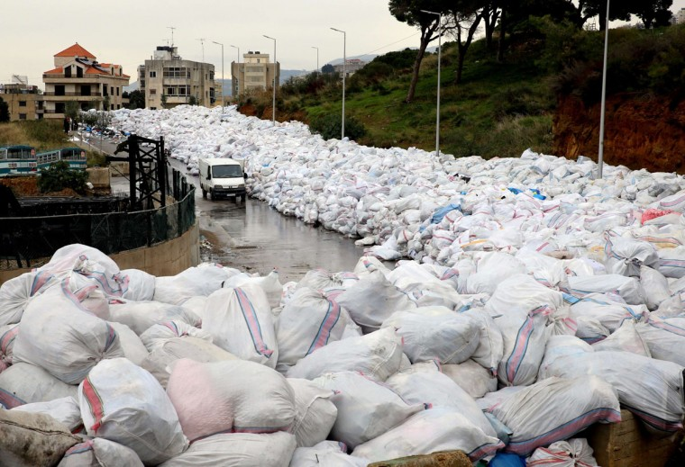 A van drives past piles of wrapped garbage blocking a newly-opened road in the town of Jdeideh northeast of Beirut on January 4, 2016 .(JOSEPH EID/AFP/Getty Images)