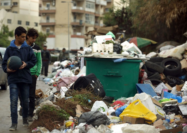 Youngsters walk past a temporary garbage dump in a suburb of the Lebanese capital, Beirut, on January 8, 2016. (PATRICK BAZ/AFP/Getty Images)