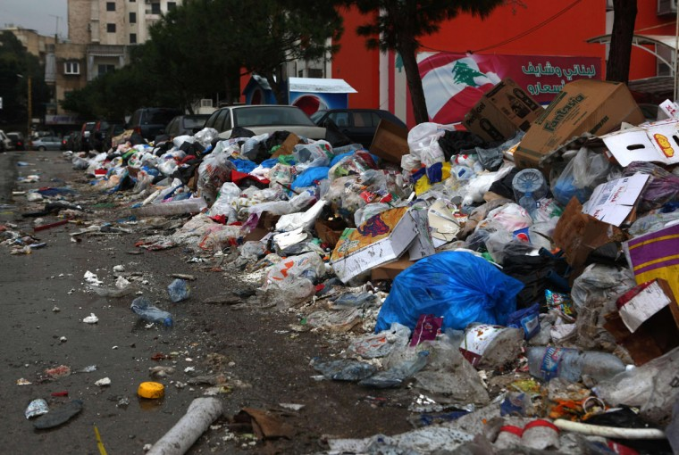 Garbage piles up in street in the town Jdeideh north east of the capital Beirut, as the Lebanese flag appears painted on a wall in the background, on January 14, 2016. (PATRICK BAZ/AFP/Getty Images)