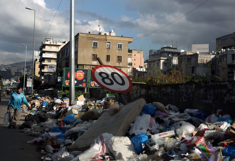 A traffic sign bends under the weight of garbage pilling up on the side of a road north of the Lebanese capital Beirut, on January 15, 2016. (PATRICK BAZ/AFP/Getty Images)