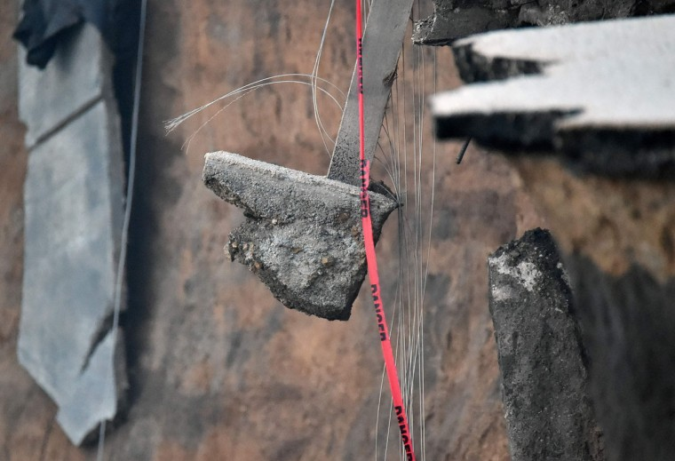 A piece of concrete hangs by a fence wire at a coastal property in Pacifica, California on January 26, 2016. Storms and powerful waves caused by El Nino have been intensifying erosion along nearby coastal bluffs and beaches in the area. (JOSH EDELSON/AFP/Getty Images)