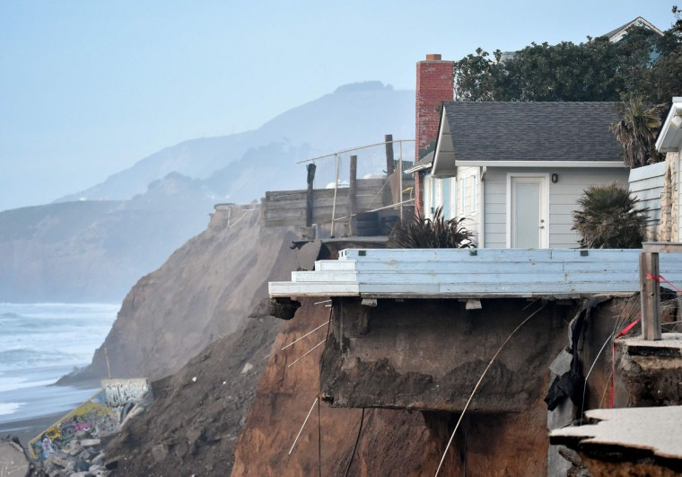 Houses hang over a cliff in Pacifica, California on January 26, 2016. Storms and powerful waves caused by El Nino have been intensifying erosion along nearby coastal bluffs and beaches in the area. (JOSH EDELSON/AFP/Getty Images)