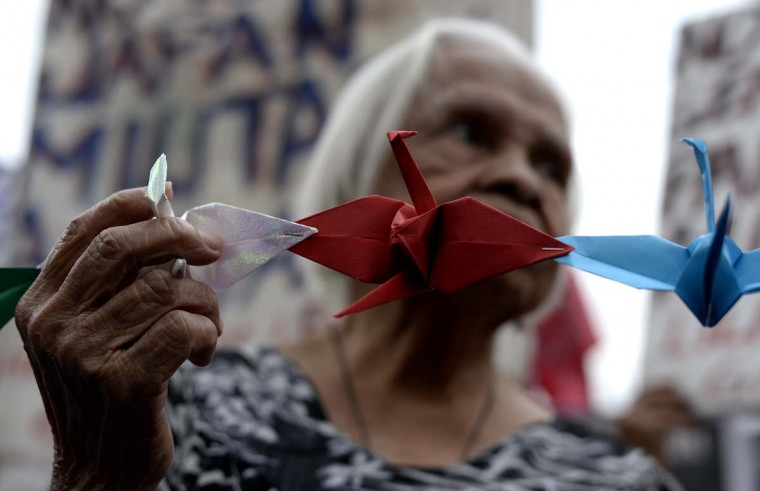 "A Filipina ""comfort woman"", a sex slave for the Japanese Imperial army during World War II, holds an origami paper peace dove as she participates in a protest near the Malacanang Palace in Manila where visiting Japanese Emperor Akihito is meeting the Philippine president on January 27, 2016. The few remaining comfort women joined the protest calling to ""right the historical wrong"" as the Japanese emperor and empress are on a five-day visit to the Philippines.     