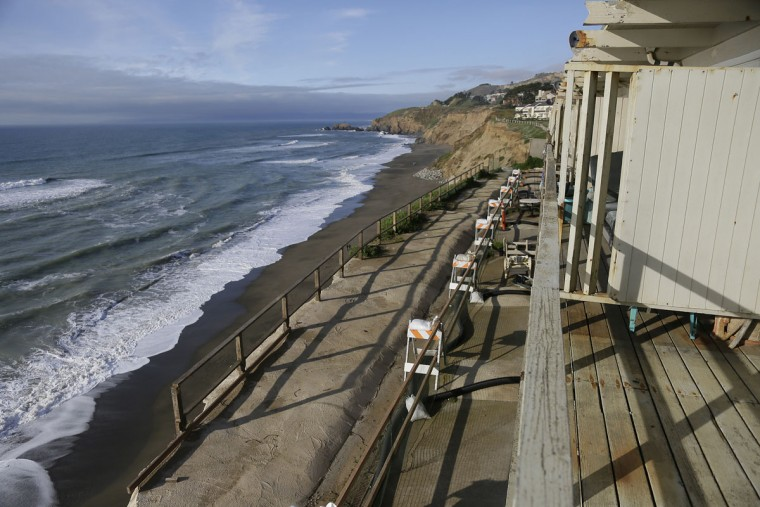 Waves crash below an apartment building that residents were forced to evacuate Monday, Jan. 25, 2016, in Pacifica, Calif. El Nino storms delivering crashing waves and powerful rain storms have put homes perched atop coastal bluffs near San Francisco in danger, forcing residents of an apartment complex on Monday to leave. (AP Photo/Eric Risberg)