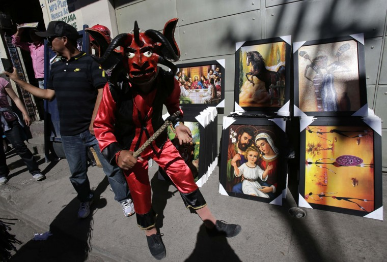 A man dressed as a 'devil' takes part in the ëDiabladaí festival, in Pillaro, Ecuador, Tuesday, Jan. 5, 2016. 'Devilsí invade this highlands town just before New Yearís and take over its streets for eight days, donning fearful masks to dance to the rhythms of local bands. The annual festival fills 12 blocks of this Andean town 60 miles (100 kilometers) south of Quito and ends on Three Kings Day, the Roman Catholic holiday. (AP Photo/Dolores Ochoa)