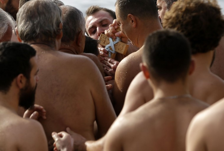 Pilgrims queue to kiss a wooden cross during an Epiphany ceremony to bless the water at the Athens' southern suburb of Paleo Faliro, Wednesday, Jan. 6, 2016. Similar ceremonies to mark Epiphany Day were held across Greece at the sea, rivers, lakes and dams. An Orthodox priest throws a cross into the water and the swimmers race to retrieve it first. (AP Photo/Thanassis Stavrakis)