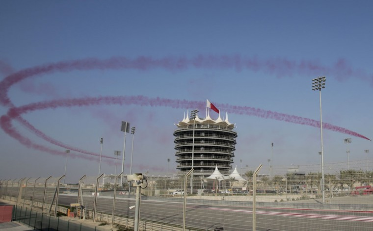 Red smoke from Saudi military jets of the Saudi Hawks Aerobatic Team circles the sky near the Bahrain International Circuit tower during the Bahrain International Airshow in Sakhir, Bahrain, Thursday, Jan. 21, 2016. Bahrain's state-run Gulf Air announced Thursday, the first day of the airshow, that it will purchase 19 new Airbus aircraft worth a listed value of $2.35 billion, part of its effort to compete in the region's race between carriers. (AP Photo/Hasan Jamali)