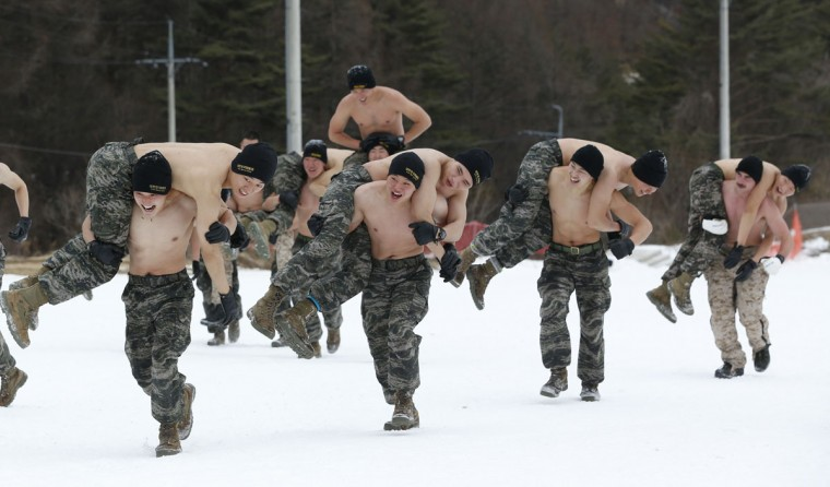 South Korean marines and U.S. Marines from 3rd Division Expeditionary Forces carry each other during a combined military winter exercise in Pyeongchang, South Korea, Thursday, Jan. 28, 2016. About 200 marines from the two countries participated the three-week winter combined exercise in South Korea. (AP Photo/Lee Jin-man)