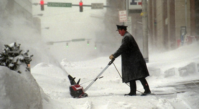 January 8, 1996 -- Don Hamilton, the Doorman at the Tremont Plaza Hotel on St. Paul St., clears the sidewalk with a snow blower. (Algerina Perna/Baltimore Sun)