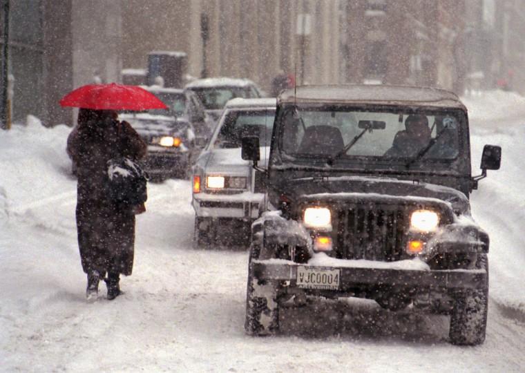 Melanie Alfano, Baltimore, makes her way towards her car through the traffic at St. Paul Place. (Algerina Perna/Baltimore Sun)