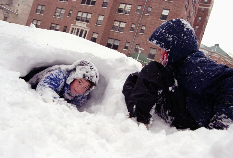 Carter Erwin, 10, left, and his 13-year-old brother Benson have dug at least eight tunnels, since Sunday, in the three feet of snow around their home at W. 39th street and Canterbury Road. (Kenneth K. Lam/Baltimore Sun)