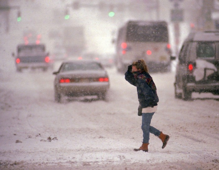 Lone pedestrian, with her face partially covered by scarf, on Baltimore St., crossing St. Paul St. during morning rush hour snow storm. (Amy Davis/Baltimore Sun)