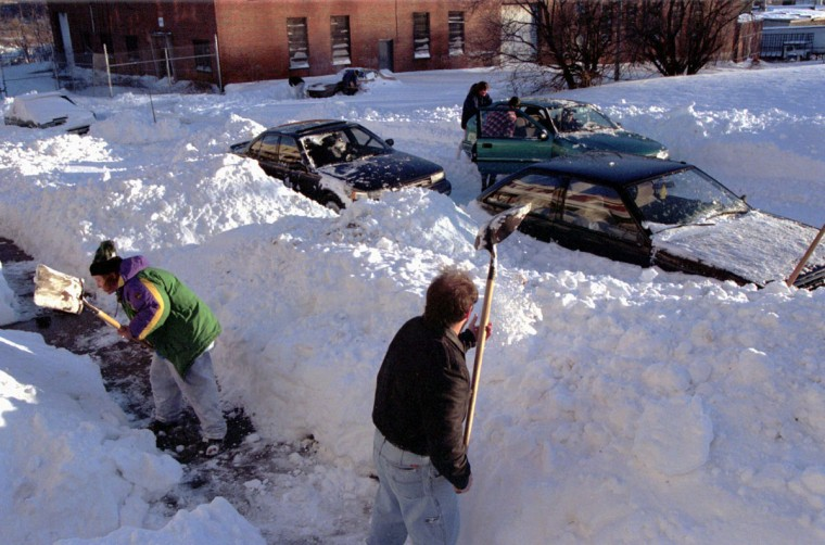 Residents along Indiana St in the Westport section of southern Baltimore shovel snow from around cars and in front of homes this afternoon Jan. 8, 1996. The neighborhood effort helped get all the cars free from being pinned by the snowdrifts. (Baltimore Sun/Karl Merton Ferron)